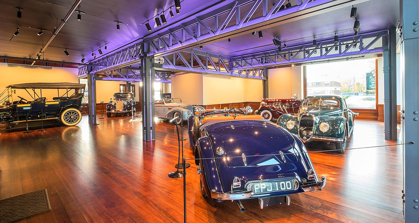 The interior of a car museum depicting 1920s, 30s, and 40s racers and luxury sedans